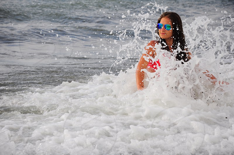 women wearing red bikini and blue tinted lens sunglasses being splash by water waves during daytime photo