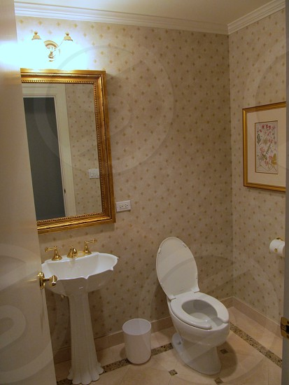 Hotel bathroom with toilet and pedestal sink photo