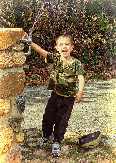 Little boy laughs as he stands under a tall park drinking fountain and lets the water fall on his head. photo