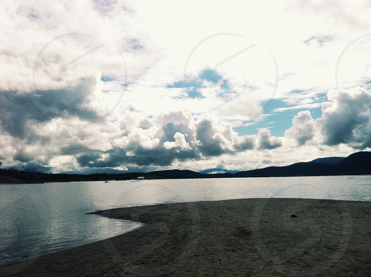 body of water under white and gray clouds and blue sky photo