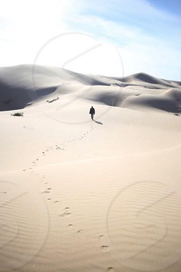 man walking across a white sand desert under a whiet cloud blue sky photo