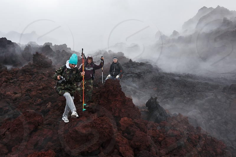 TOLBACHIK VOLCANO KAMCHATKA PENINSULA RUSSIAN FAR EAST - JULY 27 2013: Group of tourists hiking on the lava field eruption active Tolbachik Volcano on Kamchatka Region Klyuchevskaya Group of Volcanoes. photo