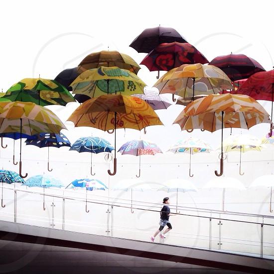 assorted umbrellas over running woman in black top photo