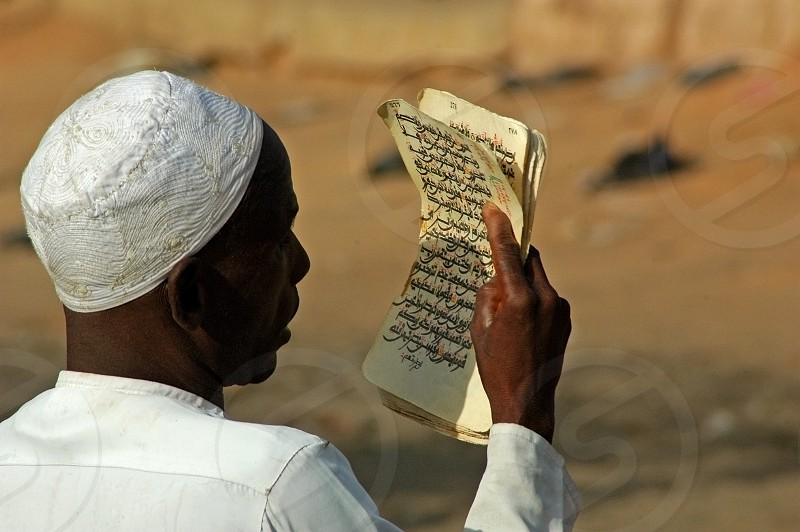 African muslim man in traditionnal white clothes reading coran extracts photo