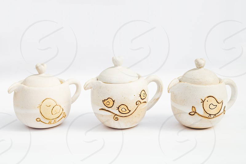 three white ceramic teapots stoneware with white background photo