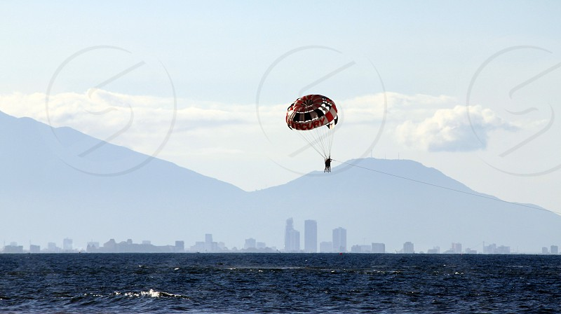 person in brown and red mercury parachute photo