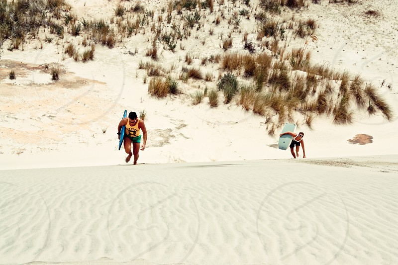 2 person trekking a sandy slope with each one holding surfboards photo