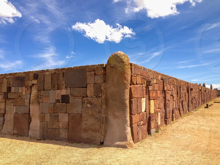 Tiahuanaco Tiwanaku La Paz Bolivia ancient Pre-Columbian archaeological history travel blue sky clouds day Spanish village sites excavations stones wall brown photo