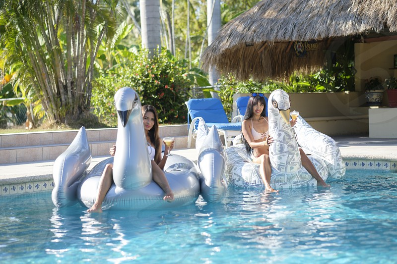 Pool Party with 2 young attractive women on giant inflatable bird pool floats Mexico photo