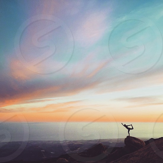 silhouette of person standing on brown rock under gray and orange clouds during daytime photo