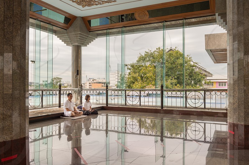 Man and woman meditating in a temple in Bangkok Thailand. photo