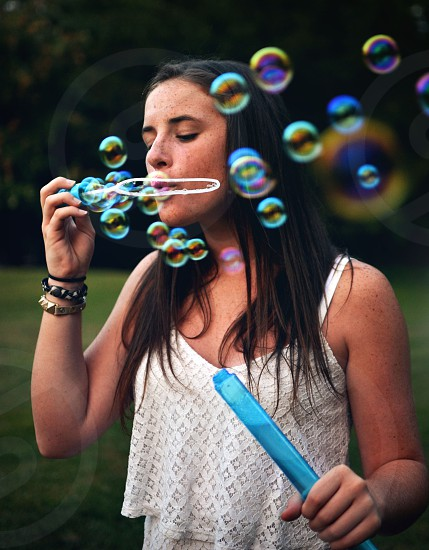 Young girl blowing bubbles photo