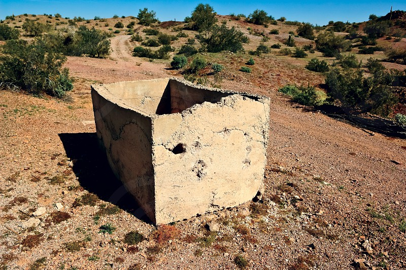 A broken concrete Bath Tub in the abandoned ghost town of Sundad Arizona. Sundad was started in the 1920s as a Tuberculosis Sanitarium but when a viable treatment was perfected in the 1940s it was abandoned. The settlement lies within federal BLM land. photo