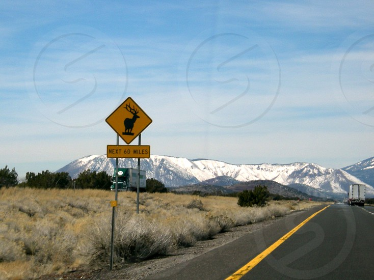 Elk sign on interstate with snow topped mountain in distance photo