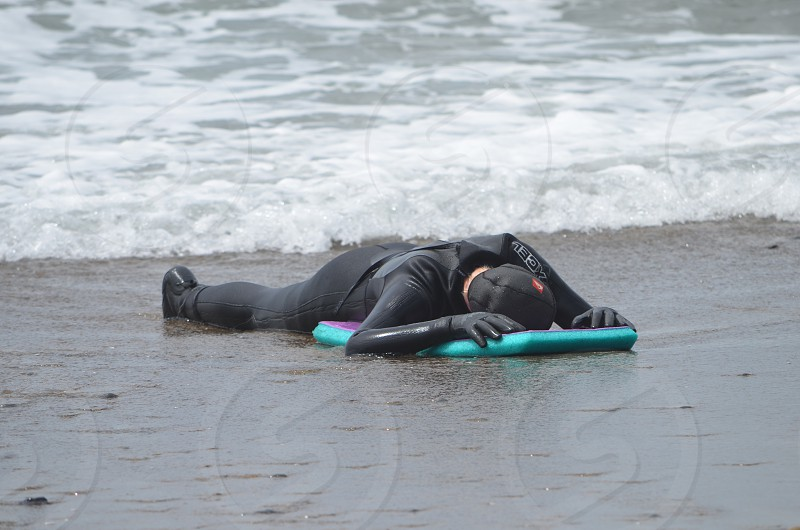 Beach sand water boy wetsuit exhausted fun photo