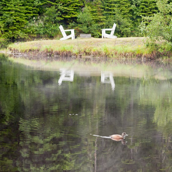 Two wooden adirondack chairs facing each other by the lake with reflection on water surface photo