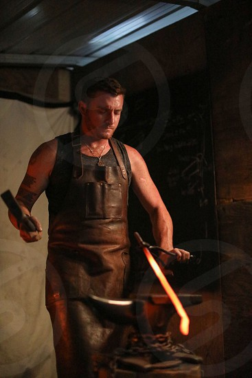 Manly forged fire intense bladesmith anvil dark male model photo