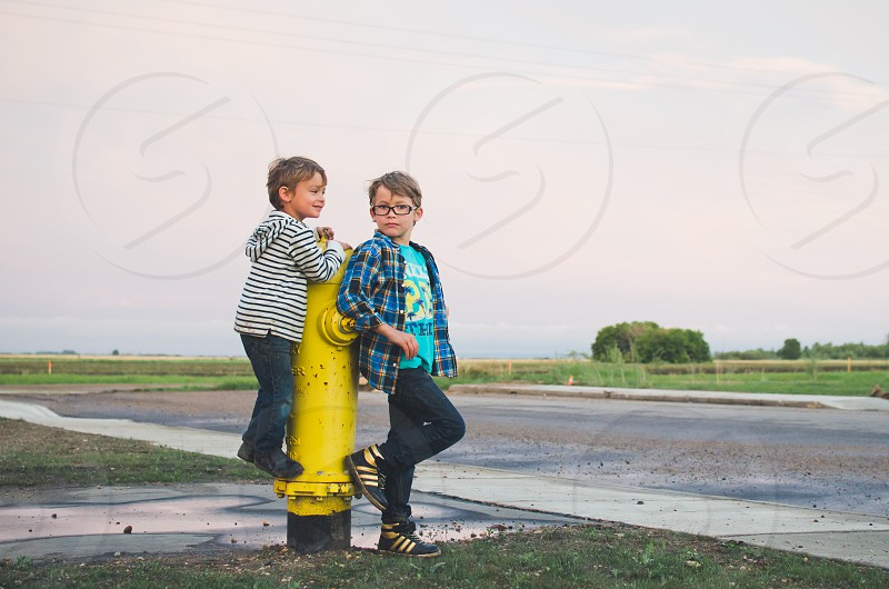 Two boys standing together outdoors with fire hydrant. photo