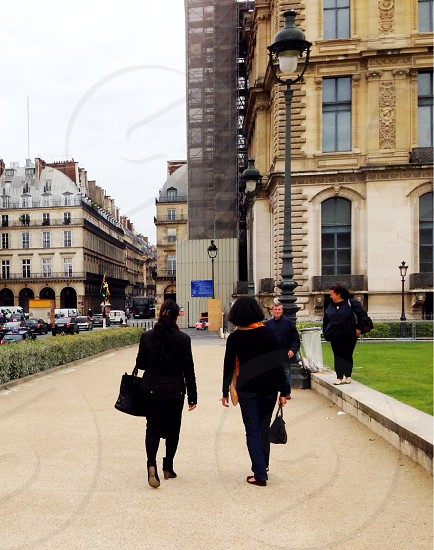 people walking towards buildings near street lamps photo