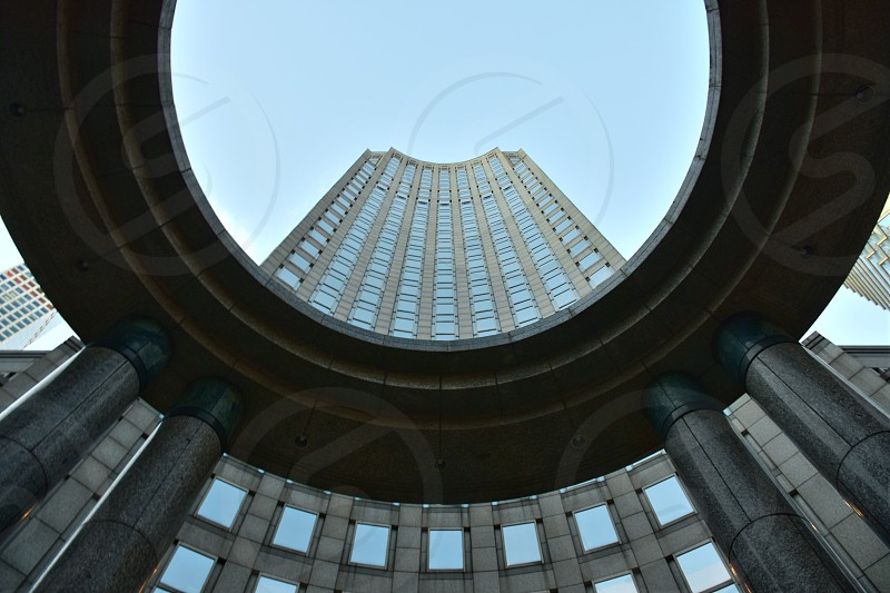 worms eye view of building with round shade under white sky during daytime photo