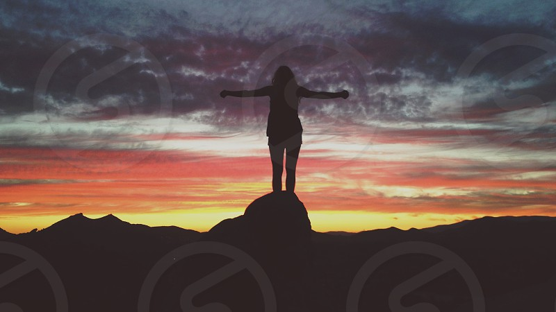 woman's silhouette standing on rock photo