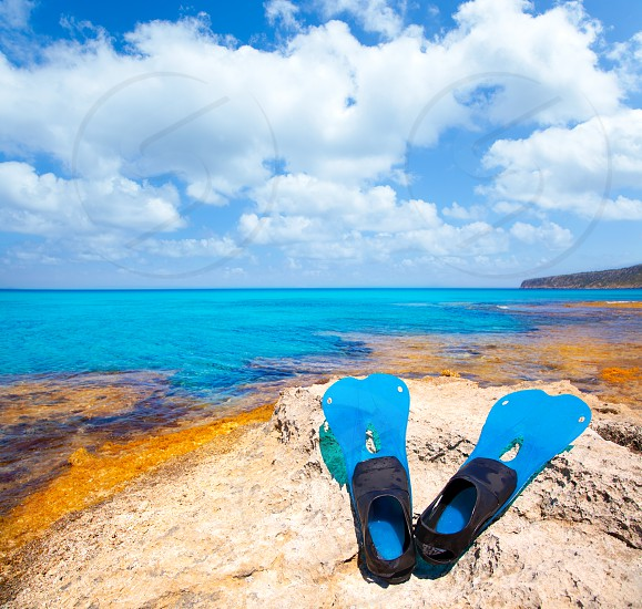 Balearic Formentera island with scuba diving blue fins on a rock photo