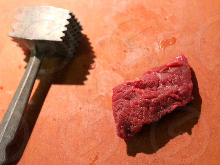 Piece of buffalo meat with metal meat hammer on orange cutting board photo