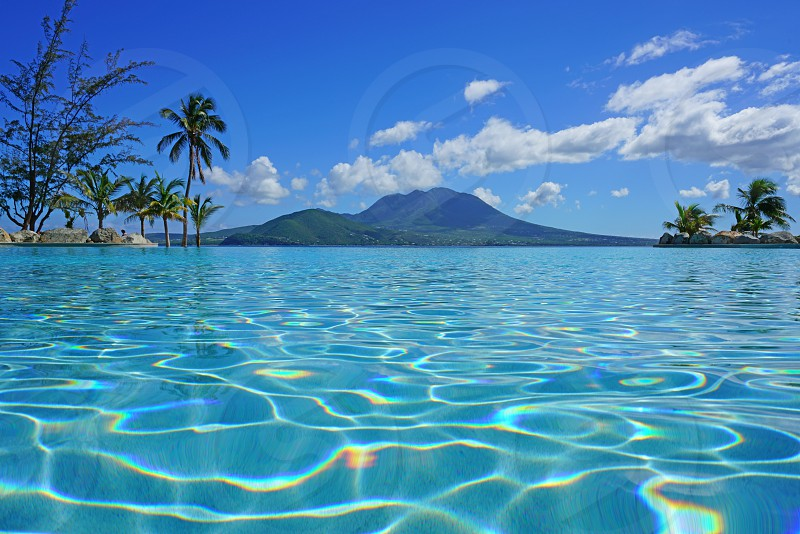 View of the Nevis Peak volcano seen from the infinity swimming pool at the luxury Park Hyatt St Kitts Christopher Harbour resort in St Kitts and Nevis photo