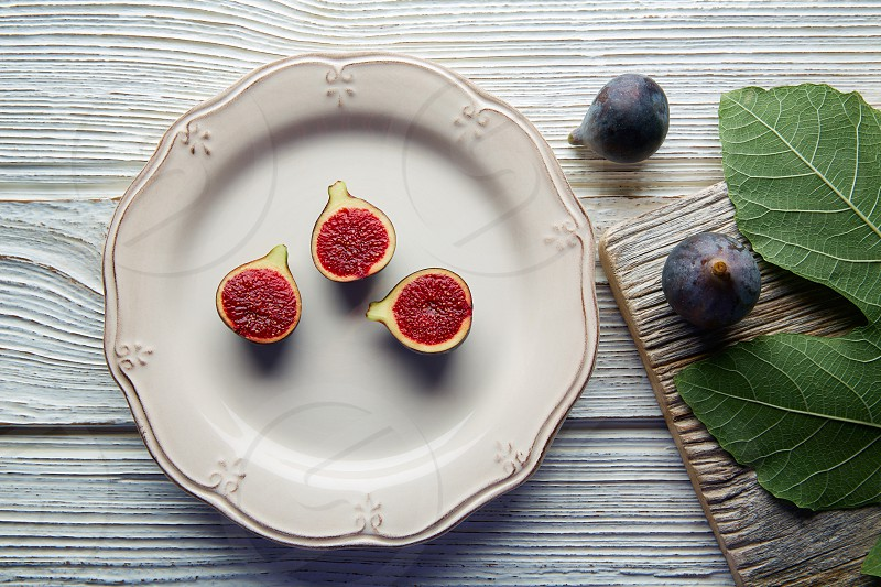 figs raw cutted fig fruits on white plate and wooden table photo