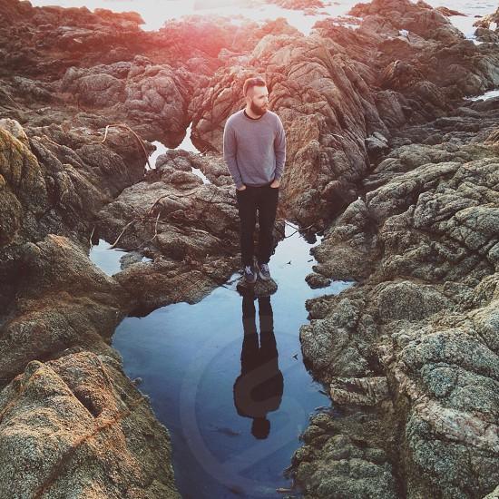 man in grey long sleeved shirt standing rock photo