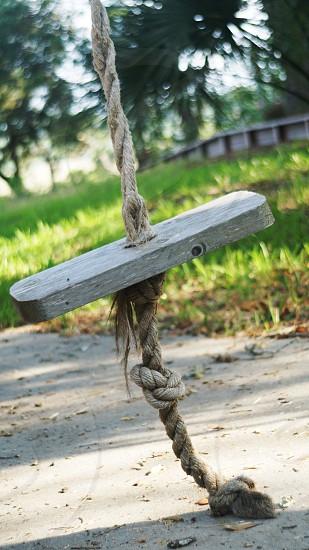 brown wooden swing with brown rope photo