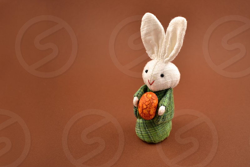 White rabbit toy. Easter bunny on a brown background. Easter rabbit with egg. Spring decoration images. Easter concept photo