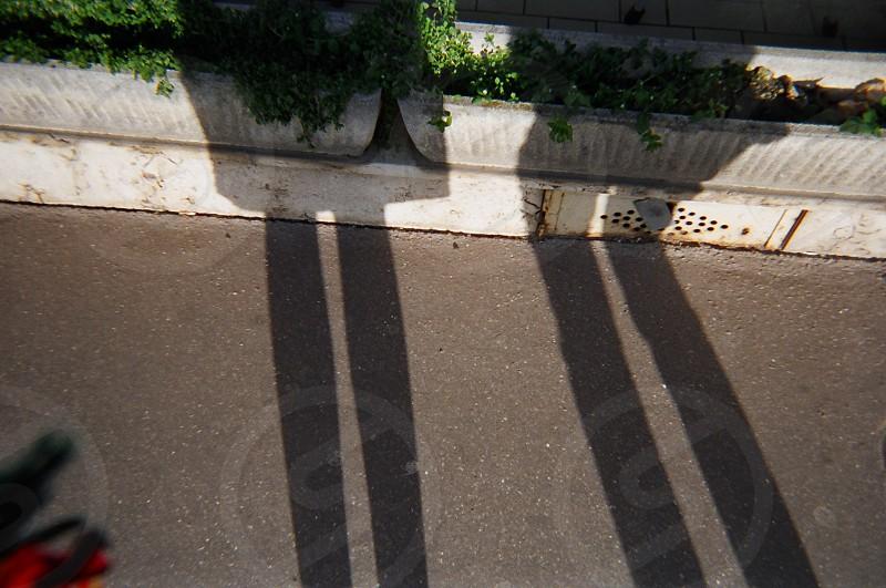 shadow of human on asphalt road photo