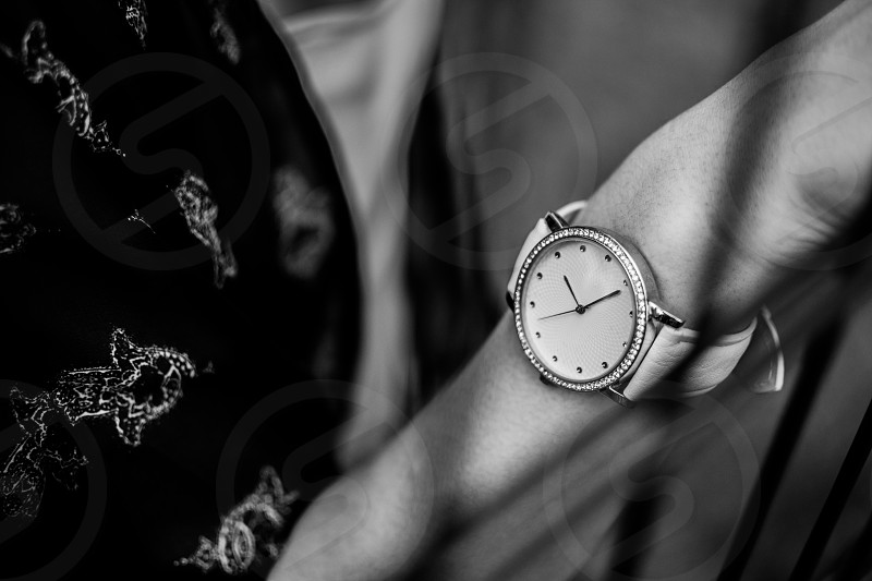 Woman wearing a watch decorated with diamonds. photo
