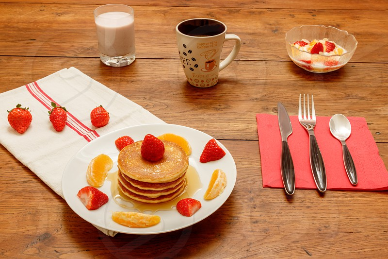 breakast on a wooden table showing a white plate whit pancakes topped with honey strawberries and orange a coffee cup a smoothie made with milk and black and red berries a bowl with cottage cheese and fruits (slice almonds orange strawberries) cutlery on a napkin and a piece of fabric.  No people. photo