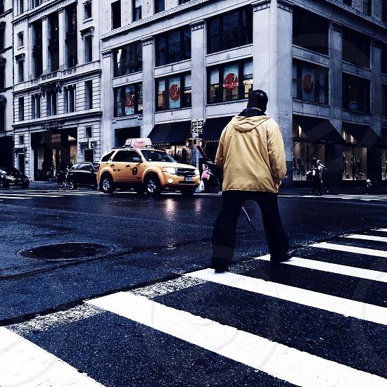 man in brown hoodie crossing street photo