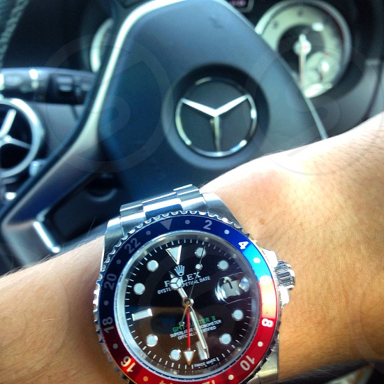 person wearing round blue and red Rolex analog watch with silver-colored link bracelet photo