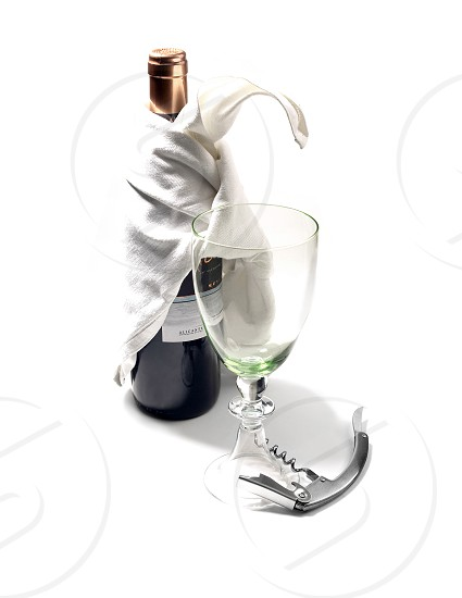 red wine bottle and glass with corckscdrew on white background photo