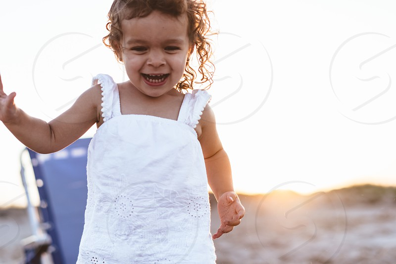 Candid; toddler running in sand; on the beach; summertime  photo