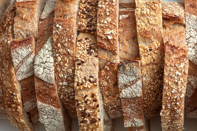 Macro photos of slices of homemade grain bread with sesame seeds and flax. Organic Healthy Food. Flat lay photo