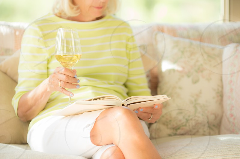 Woman sitting on a couch reading a book with a glass of wine in her hand. photo