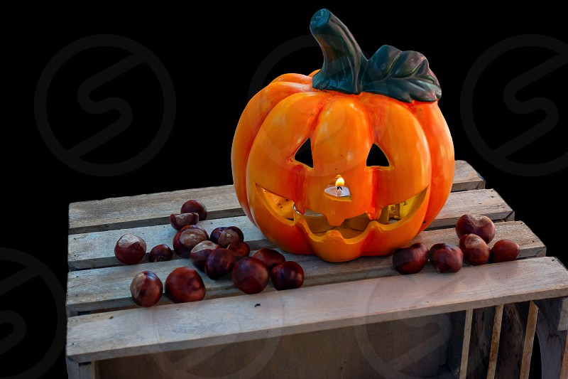 Halloween Pumpkin with Chestnuts Decoration on wooden box autumn holiday concept burning candle seen through nose candle flickering in wind isolated on black photo