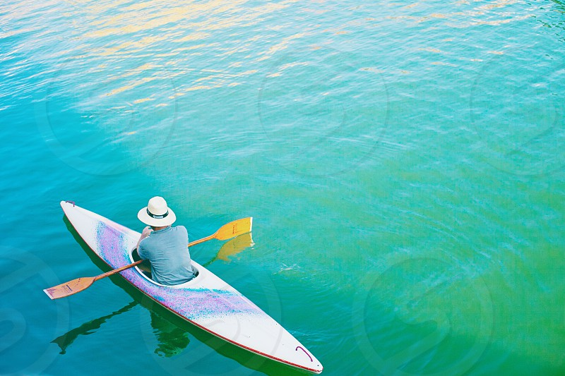 person in blue t shirt riding kayak  floating on water photo