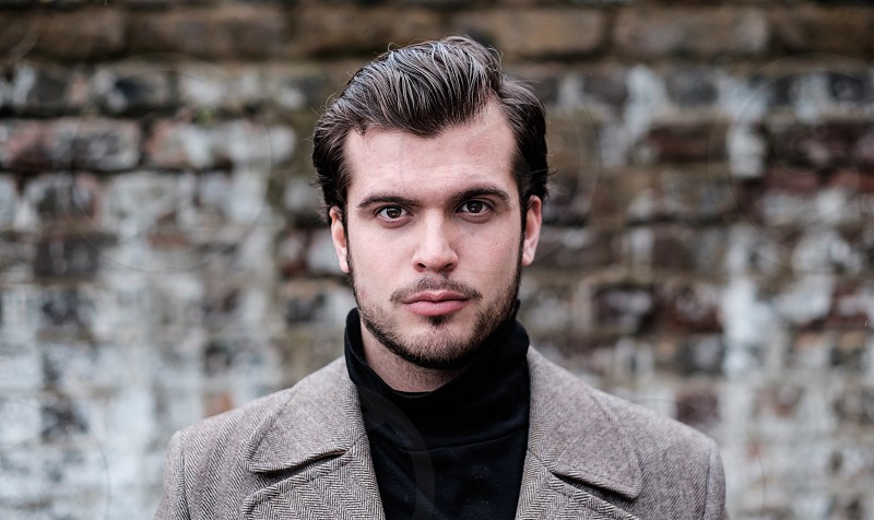 Dark haired young man portrait with facial hair black polar neck turtle neck and a tweed jacket emotionless expression slick back hair looking at the camera. photo