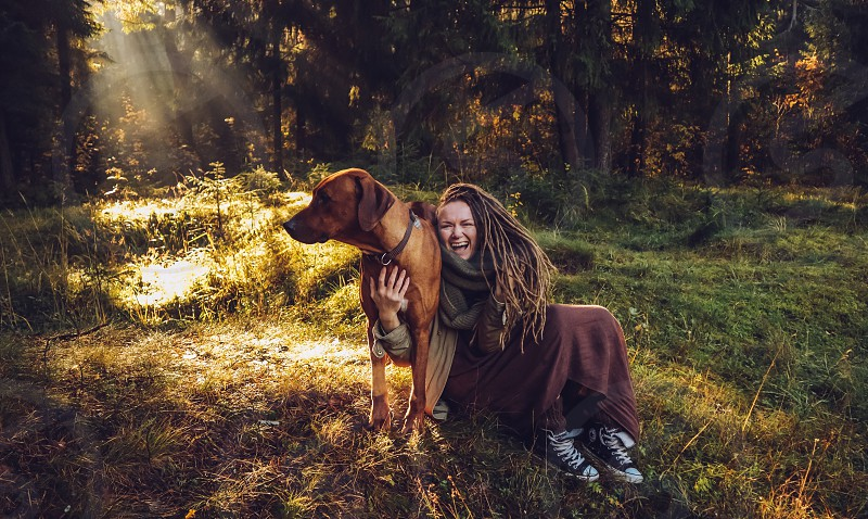Young smiling woman with dreadlocks in autumn fall forest in the morning sunshine playing with a dog ridgeback photo