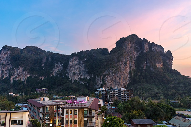 Ao Nang Krabi Province Thailand - January 22 2019: View on big cliff and hotels buildings in the evening at sunset twilight photo