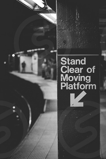 Stand Clear of Moving Platform signage mounted on post photo