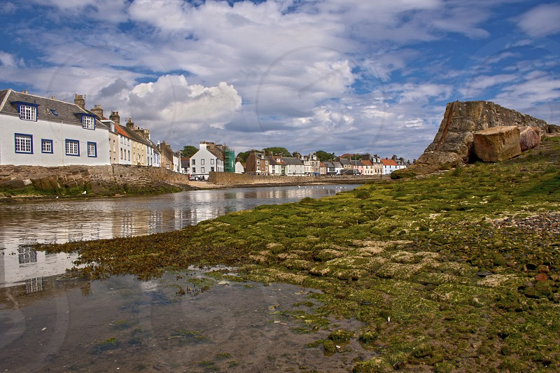 Scottish village of Anstruther under blue skies with cottages lining the water and green moss-covered boat ramp in foreground. photo