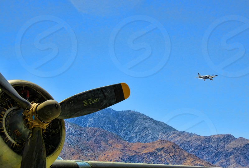 On a desert airfield a small plane takes off in the background while an old propeller plane is in the foreground photo