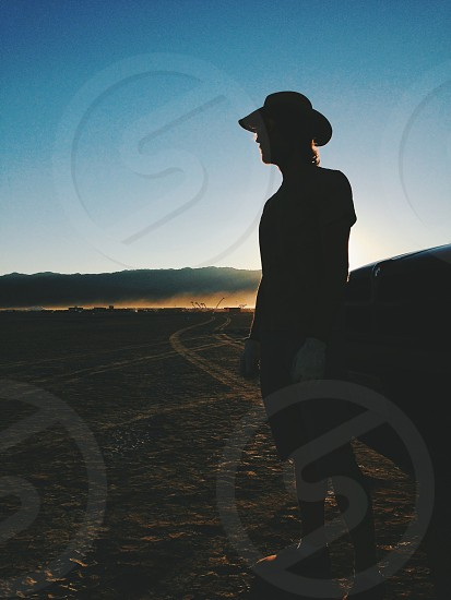 Silhouette of a man in the desert looking off in the distance photo